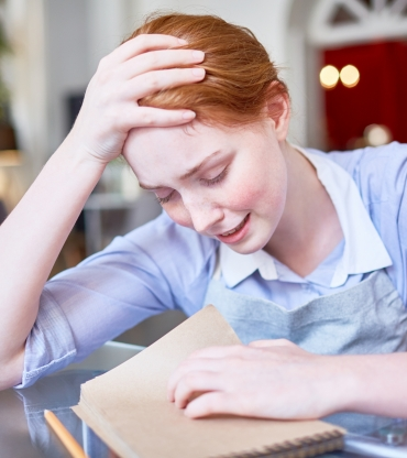 Tired and unhappy young waitress crying over her notepad after working day