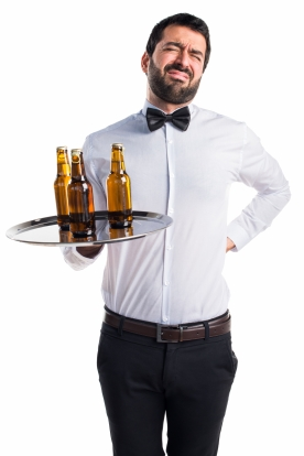 Waiter with beer bottles on the tray with back pain